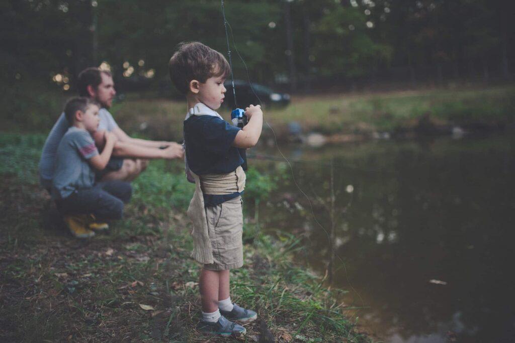 Ein kleiner Junge holt seine Angelroute ein