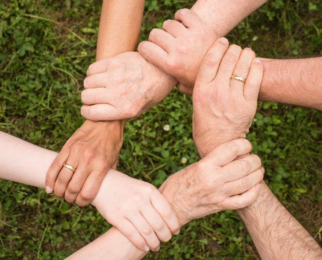 6 Hände halten sich in einem Kreis gegenseitig fest