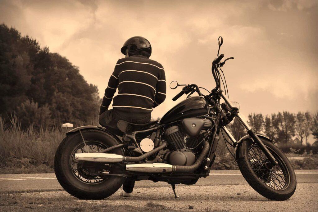 Motorradfahrer macht am Straßenrand eine Pause und sitzt auf seinem Gefährt