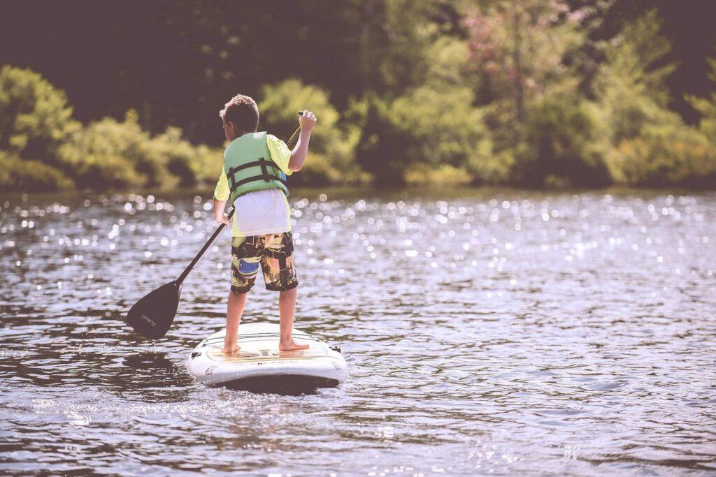 Ein kleiner Junge auf einem Stand-Up-Paddle bei schönem Sonnenwetter auf dem See